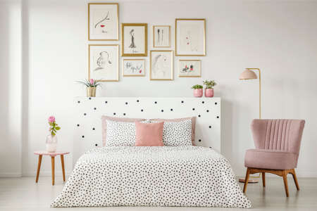 Feminine bedroom interior with a double bed with dotted sheets, armchair, art collection and plants
