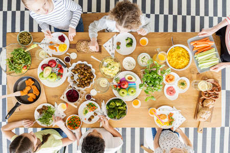 Top view on children eating healthy food during friends birthday party