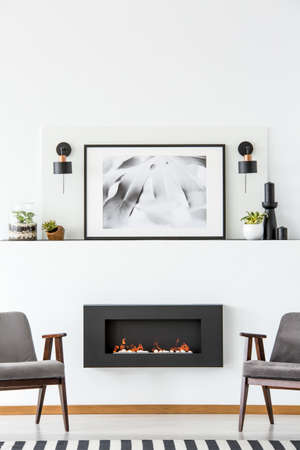 Black fireplace between grey armchairs in white flat interior with poster between lamps. Real photo Фото со стока - 102704254