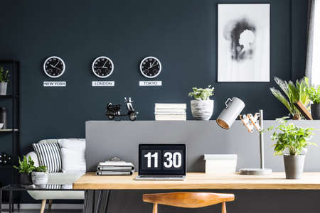 Laptop on wooden desk with lamp and plant in modern home office interior with poster 版權商用圖片