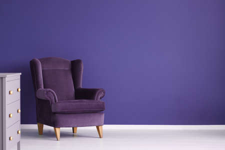 Purple velvet armchair against violet wall in cozy living room interior with cabinet and copy space