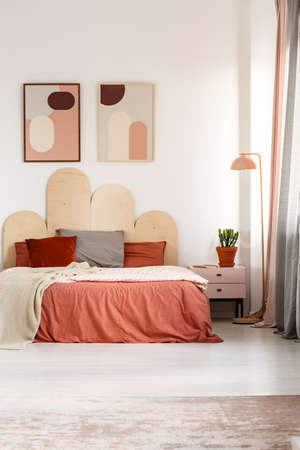 Posters above bed with orange sheets in pastel bedroom interior with plant and lamp. Real photo