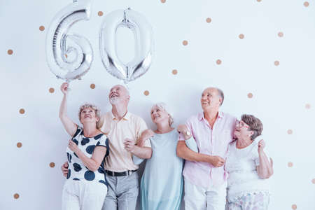 Grandmother and grandfather with silver balloons celebrating 60th birthday Stok Fotoğraf