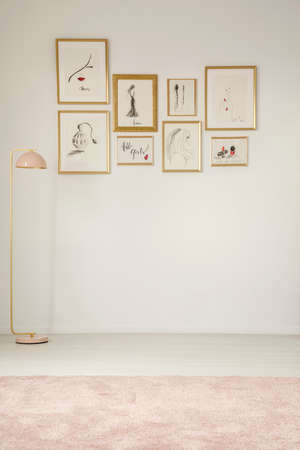 Paintings in golden frames on the white wall, pastel lamp and carpet in an empty room interior Stockfoto