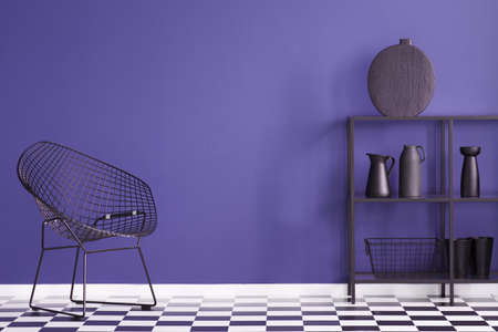 Black armchair on checkerboard floor in violet living room interior with vase on a shelf