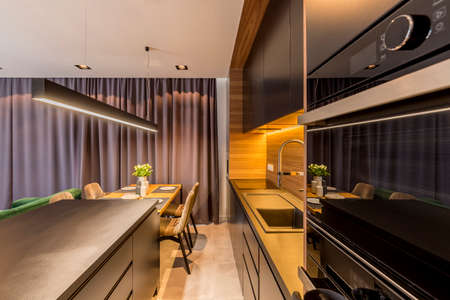 Dark kitchen in open space interior with chair at dining table against grey drapes