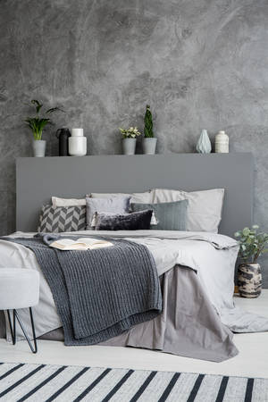 Dark blanket on bed with headboard in grey bedroom interior with concrete wall. Real photo