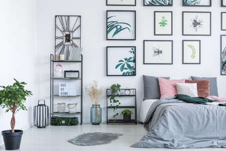 Real photo of a bed standing next to the shelves with ornaments and plants in bedroom interior with paintings on a wall