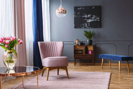 Real photo of a pink armchair standing on a rug and under a lamp in spacious living room interior, next to a table with flowers and in front of a shelf next to a grey wall with dark painting