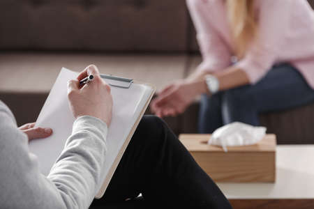 Close-up of therapist hand writing notes during a counseling session with a single woman sitting on a couch in the blurred background. Stockfoto