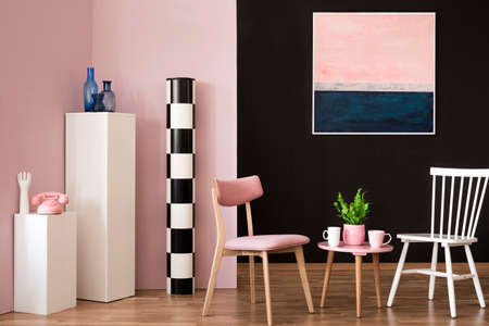 Pink and white chair at table in living room interior with painting and phone on pedestal