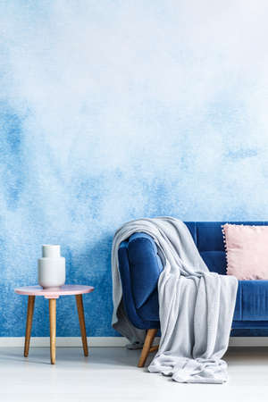 Cropped photo of a couch with a grey blanket next to a stool with a white vase in a living room interior with an empty wall 写真素材