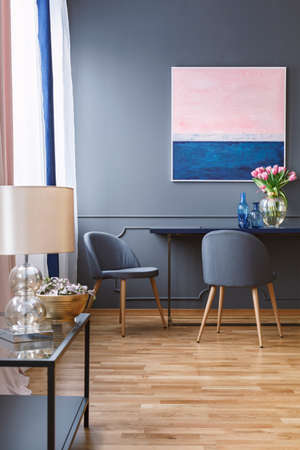 Real photo of a spacious dining room interior with a blue and pink painting on a grey wall, above a table and two chairs and with a table with lamp in the front