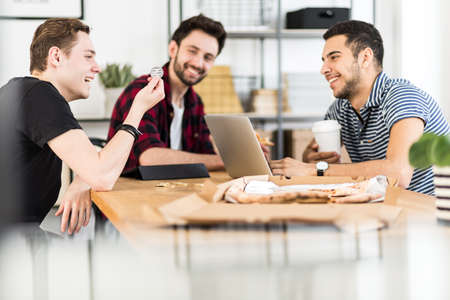 Group of friends smiling and looking at a token in a an office