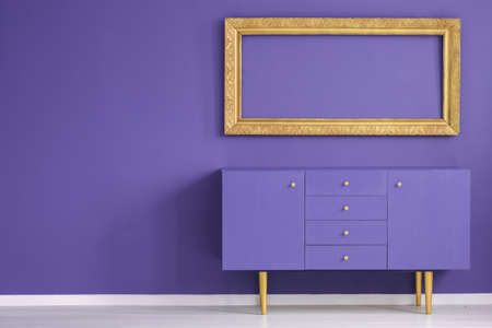 Mockup of gold empty frame above violet cabinet in anteroom interior with copy space