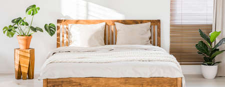 Close-up of double wooden bed with bedding, pillows and blanket against white wall in a bright sunny bedroom interior. Two green plants standing beside. Panorama. Real photo. 스톡 콘텐츠 - 102789339