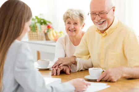 Happy senior man and his wife conversing with financial advisor about a loan Stock Photo