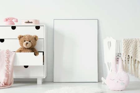 Knuffel in kastje naast poster met mockup en wiegje in babykamerinterieur. Echte foto. Plaats voor uw afbeelding