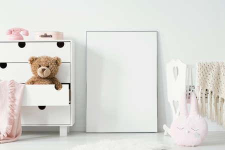 Plush toy in cabinet next to poster with mockup and cradle in baby's bedroom interior. Real photo. Place for your graphic