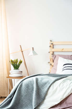 Grey blanket on bed in bright minimal bedroom interior with lamp and plant on table. Real photo Archivio Fotografico - 102789607