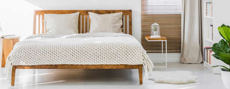 Front view of a simple wooden double bed with cushions and thick weaved cover in a white sunny bedroom interior. Panorama. Real photo. 스톡 콘텐츠 - 102834253