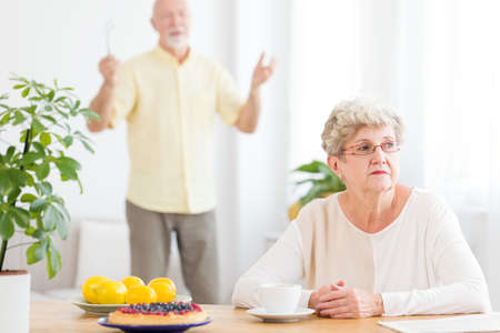 Sad senior woman arguing with her husband standing in blurred background