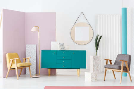 Modern living room interior with two armchairs, pastel pink lamp, turquoise cupboard and decorative marble pillars Stock Photo