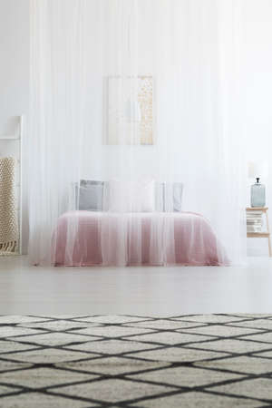 Patterned carpet in scandi bedroom interior with white veil above bed. Real photo