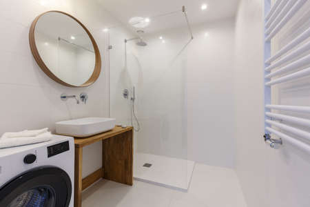 Mirror above washbasin in white bathroom interior with shower and washing machine. Real photo Фото со стока