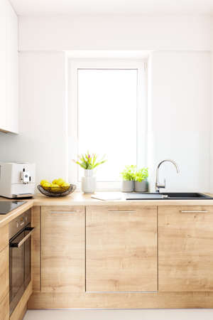 Flowers on wooden countertop in bright kitchen interior with window. Real photo