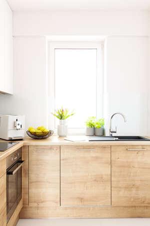 Fiori sul piano di lavoro in legno all'interno della cucina luminosa con finestra. Foto reale