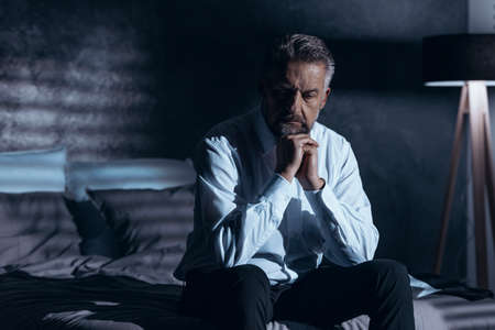 Stressed and depressed man sitting alone in the dark with a problem