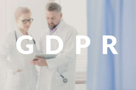 Two doctors sharing tips and information about the new legislation concerning data protection. GDPR banner on a blurred photo