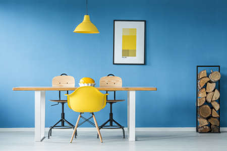 Yellow accents in a blue dining room interior with a big table, poster and firewood log rack