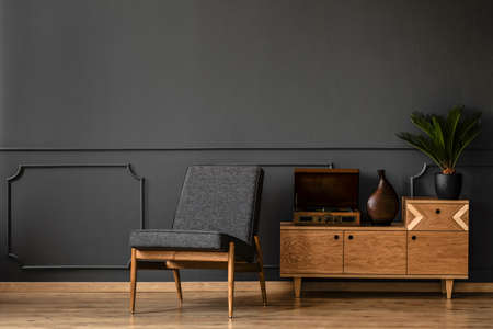 A gramophone on wooden cabinet and black chair in dark retro room interior Stock fotó