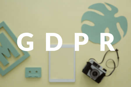 GDPR in a creative business concept. Blurred photo of a photographers desk with a tablet and a vintage camera. White banner in the front Stock Photo