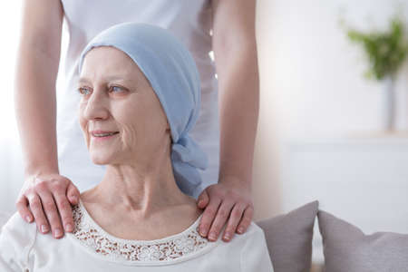 Smiling elderly woman with cancer in remission supported by her daughter Stock Photo - 102918169