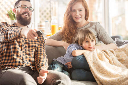 Happy family watching TV together on the sofa in the modern living room Фото со стока