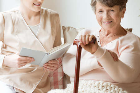 Close-up of smiling senior woman with walking stick and friendly nurse