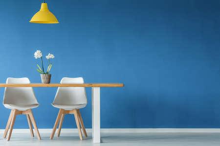 Dos sillas, flor, lámpara amarilla y mesa de madera en una pared azul, vacía en el interior del comedor