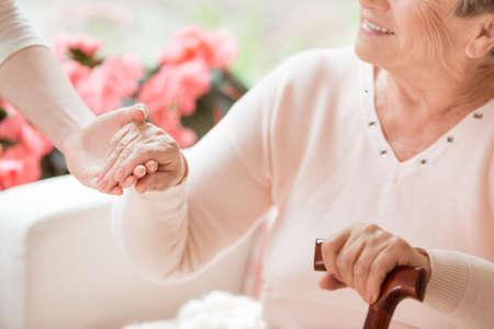 Close-up van verzorger ondersteunende lachende senior vrouw met wandelstok