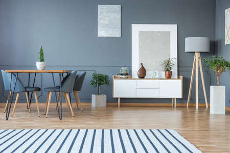 Modern dining room interior with a striped rug, table, grey chairs and white cabinet Stock Photo