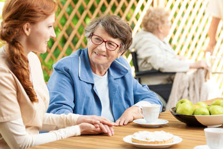 Happy grandmother drinking tea and caregiver taking care of her