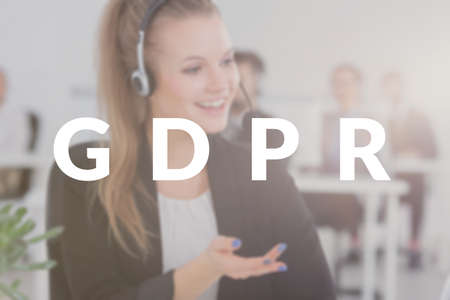 Young consultant working in a contact center calling the customers in connection with the new GDPR law. Blurred photo with a white banner