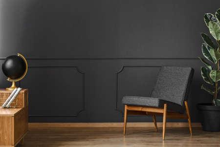 Spacious, black retro room interior with black walls, chair, wooden floor and cupboard Stockfoto