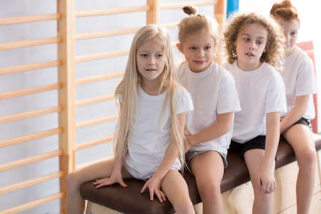 Kids in sport outfits sitting at the gym before gymnastics classes
