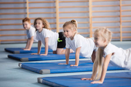 Happy girl exercising on a blue mat during corrective gymnastics classes