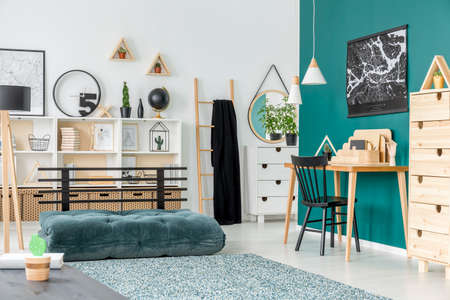 Black chair at wooden desk in kids room interior with green mattress near patterned carpet