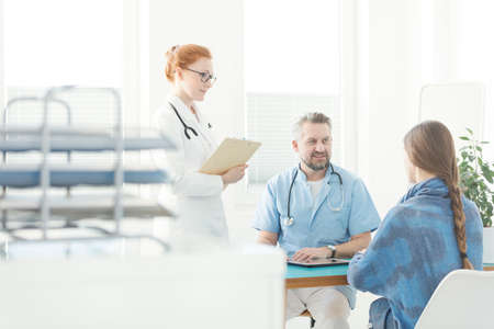 Friendly gynecologist and nurse talking to a patient in the office Stock Photo