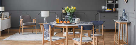 Grey wooden armchair in open space interior with chairs at round dining table with yellow flowers Stock Photo